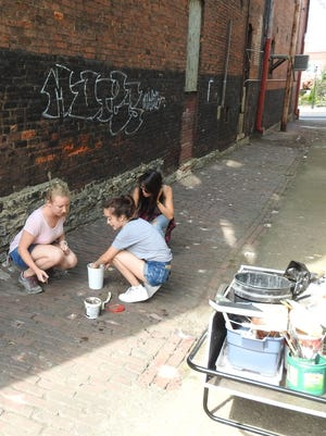 Hillary Hendricks, Kristen Santozzi and Shannon Kim, members of the Zanesville Art Residency, use broken pottery pieces found along the river to fill gaps in the brick road in the alley behind Yan Sun's Museum.