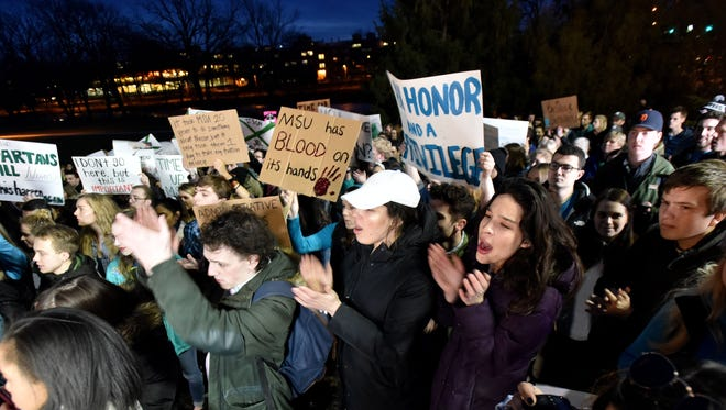 """Demonstrators gather at """"The Rock"""" on MSU's East Lansing campus on Friday to support victims of Larry Nassar and call for more changes in leadership."""
