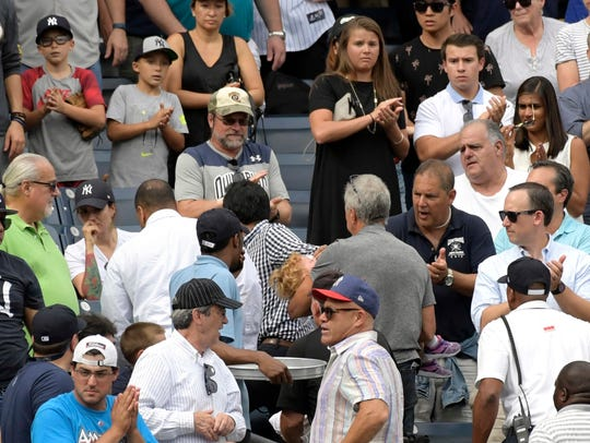 Baseball fans react as a young girl is carried out