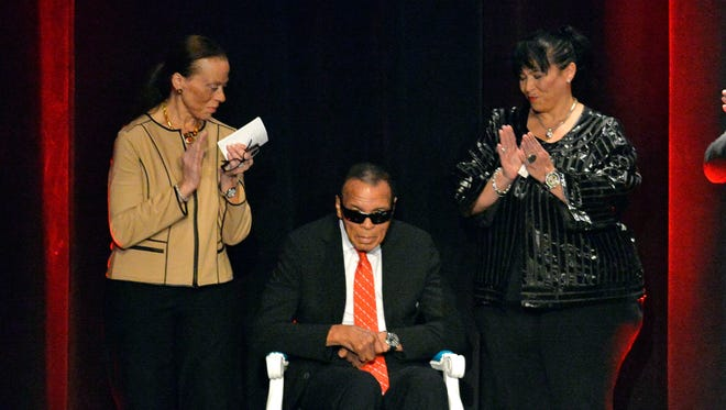 In a file photo from 2015,  Muhammad Ali, center, is cheered by the audience as his wife Lonnie Ali, left, and his sister in law Marilyn Williams look on, as he is awarded the Grawemeyer Spirit Award  in Louisville, Ky.