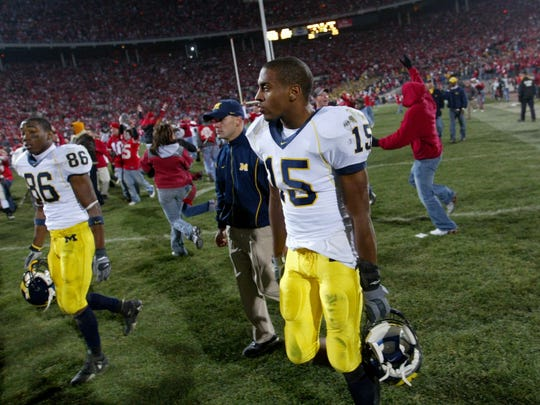 Michigan's Mario Manningham (85) and Steve Breaston (15) walk off the field after losing 42-39 on Saturday, Nov. 18, 2006 in Columbus, Ohio.