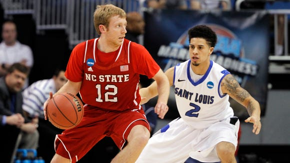 North Carolina State Wolfpack guard Tyler Lewis (12) drives against Saint Louis Billikens guard Austin McBroom (2) during the first half of a men's college basketball game during the second round of the 2014 NCAA Tournament at Amway Center, March 20, 2014.