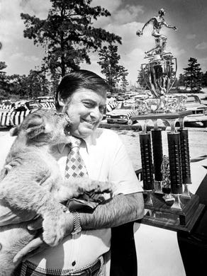 1976: A playful lion cub muzzles T.C. Freeman, director of park quality at Great Adventure,  winners bowling trophy to the right.