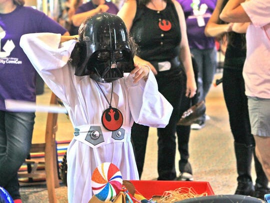 Kaleigh Fouchey, dressed as Princess Leia from the 'Star Wars' movie series, tries on a Darth Vader mask at a photo booth at Electric City ComiCon at the Anderson County Library in Anderson.