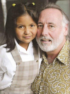Country music industry executive Steve Moore with Ana Rios in Guatemala City a few years after Moore arranged for the girl to come from Guatemala City to Nashville to have a bullet removed from her sternum. Ana is wearing a school uniform for the Shalom School, built by the Shalom Foundation, founded by Moore.