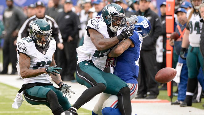 Philadelphia Eagles cornerback Nolan Carroll (23) watches as free safety Malcolm Jenkins (27) hits New York Giants wide receiver Odell Beckham (13) to break up a pass in the first half during the game at MetLife Stadium.