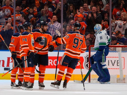 Vancouver Canucks goalie Anders Nilsson (31) looks on as the Edmonton Oilers celebrate a goal during first-period NHL hockey game action in Edmonton, Alberta, Saturday, April 7, 2018. (Jason Franson/The Canadian Press via AP)