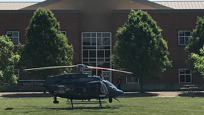 A police helicopter is seen on the lawn at Noblesville West Middle School in Noblesville, Ind., about 30 miles northeast of Indianapolis, where a shooting occurred May 25, 2018.
