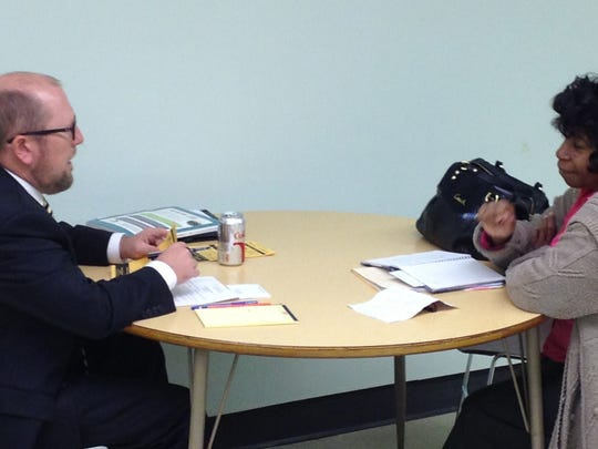 Ned Mulligan, an attorney at Cohen & Malad, gives free legal advice to Delores Fatherree of Indianapolis during the Indianapolis Bar Association's Ask a Lawyer program in October 2013 at the Indianapolis Marion County Public Library branch on East Washington St.