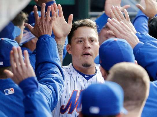 New York Mets' Wilmer Flores is greeted by teammates