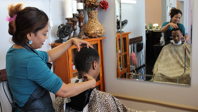 Paul Muragizi, a student at the University of Nebraska in Abilene for the summer, gets his first haircut at Best Clips. Formerly Classic Salon, operator Dhipa Rani Hamilton moved her business west to near the future Abilene Police Department headquarters.