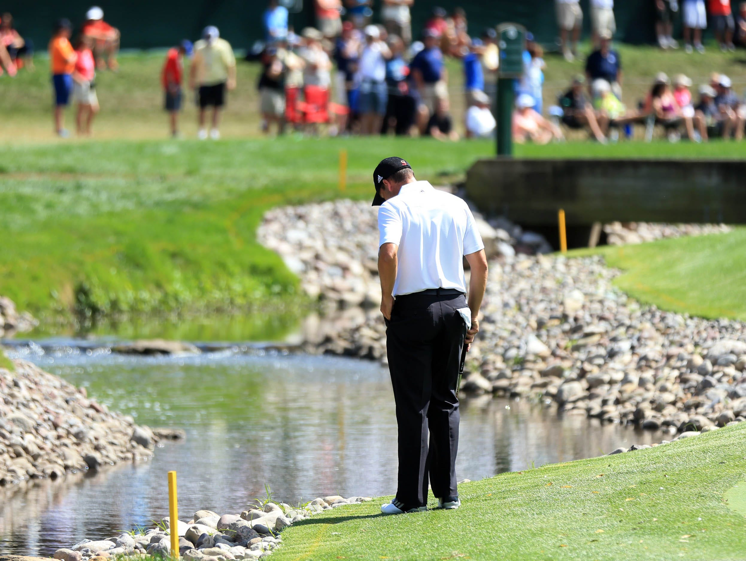 Sergio Garcia looks for his ball in the hazard on the fifth hole.