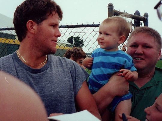 Russell Beckman holds his son Zachary while meeting