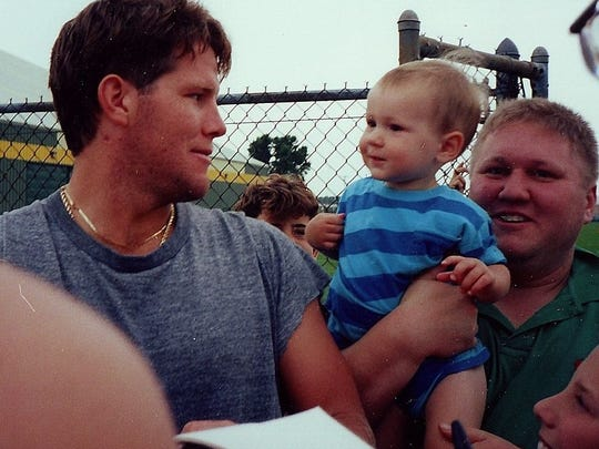 Russell Beckman holds his son Zachary while meeting Brett Favre in 1992. The Pro Football Hall of Fame quarterback had yet to play a down for the Packers.