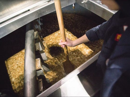 A brewer at Chelsea Craft Brewing stirs a mixture of