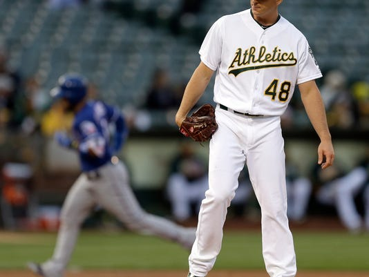 Oakland Athletics' Eric Surkamp, right, waits for Texas Rangers' Robinson Chirinos to run the bases after hitting a three-run home run during the second inning of a baseball game Tuesday, June 14, 2016, in Oakland, Calif. (AP Photo/Ben Margot)