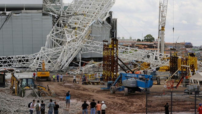 People stand in front of a metal structure that buckled on part of the Itaquerao Stadium.