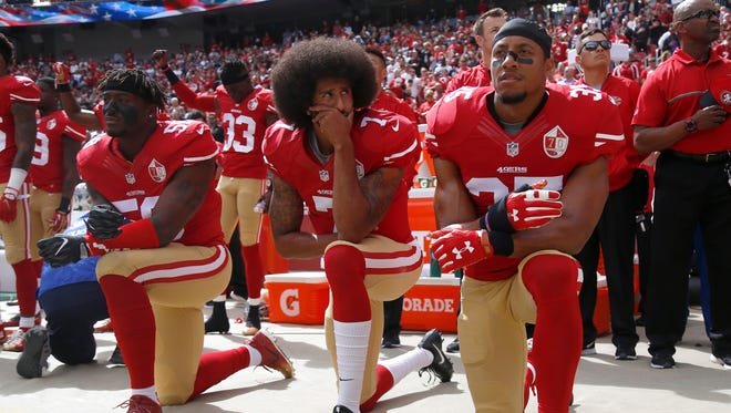 From left, San Francisco 49ers Eli Harold (58), quarterback Colin Kaepernick (7) and Eric Reid (35) kneel during the national anthem before their NFL game against the Dallas Cowboys on Sunday, Oct. 2, 2016 at Levi's Stadium in Santa Clara, Calif.