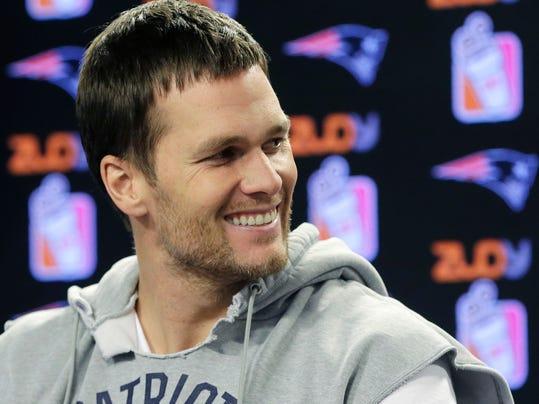 New england patriots quarterback tom brady smiles while taking