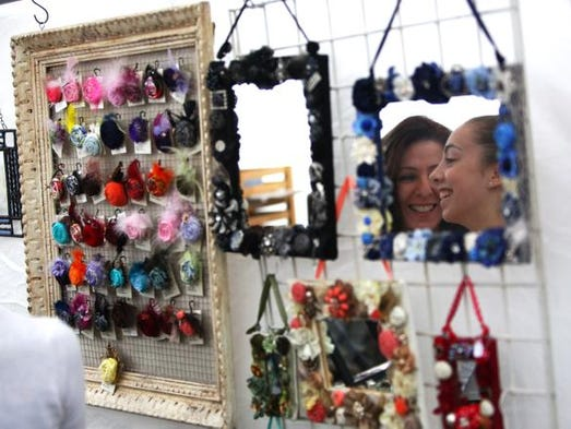 Elaine Bakewicz and her daughter Lauren Bakewicz, 14, both of Webster share a moment while shopping for accessories at the  Clothesline Festival on Sept. 7.