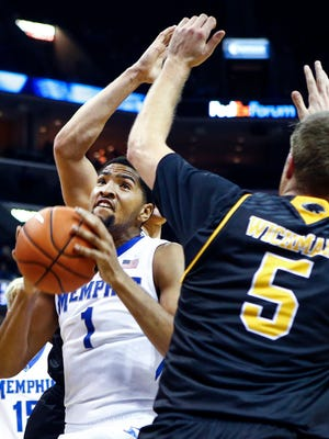 University of Memphis forward Dedric Lawson (left) drives to the basket against Milwaukee forward Cody Wichmann (right) during first half action at FedExForum.