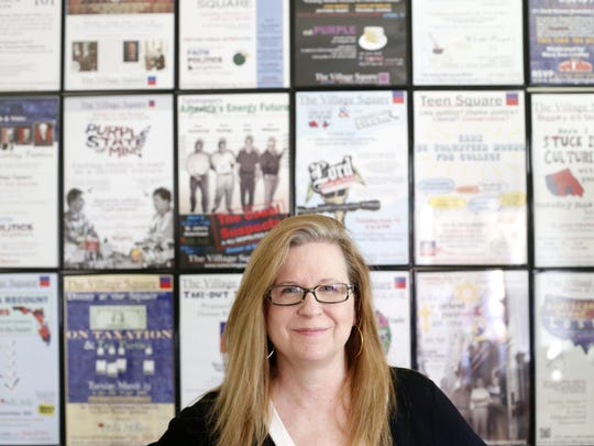 Liz Joyner, executive director of The Village Square events, stands at her home in front of eight years of posters for the various incarnations of the community discussions.