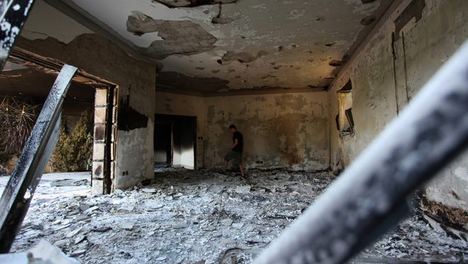 A man walks in the rubble of the U.S. consulate Sept. 13, 2012, after an attack that killed four Americans, including Ambassador Chris Stevens in Benghazi, Libya.