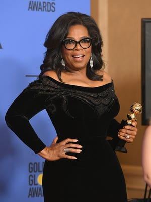 Oprah Winfrey poses with the Cecil B. DeMille Award in the press room during The 75th Annual Golden Globe Awards.
