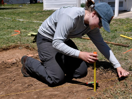 Heather Young, an archaeologist with the National Park Service, measures the depth of the pit she is excavating at the Robert E. Howard home in Cross Plains Wednesday. The NPS is excavating the storm cellar behind the home of the celebrated author, who died in 1936 and was best known as the creator of Conan the Barbarian.