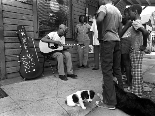 "Furry Lewis, legendary bluesman, performs for neighbors August 13, 1976 near the Memphis duplex at 811 Mosby where he had lived for six years. 83 at the time, Lewis suffered from cataracts. He said he couldn't see anything but shadows and visitors had to speak up and identify themselves before he could decide what to do about the teeth. With close friends, he didn't mess with appearances. But with others - some of them strangers who come by - he would say, "" Hold on, lemme put my teeth in for you."" Then he would take them out of the jar, pop them into his mouth, snap at the air, grin broadly, and ask, ""How I look?"" Speaking to a reporter at the time, he said; ""You know what I wish? I wish I would live forever and that you would never die. That proves I'm lookin' out for you, don't it?"" Lewis died September 14, 1981."