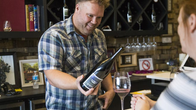 Manager Phillip Brown serves wine at the Southwest Wine Center Tasting Room in Clarkdale.