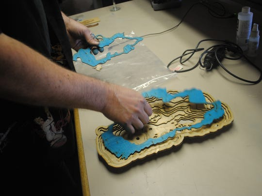 Roger Floren uses a wood mill and a three-dimensional laser to create a layered replica of Lake Tahoe, a replica which was on display Monday at the Bridgewire arts incubator in Sparks. Floren demonstrates the use of a mold, which helps Floren put each layer in place correctly.