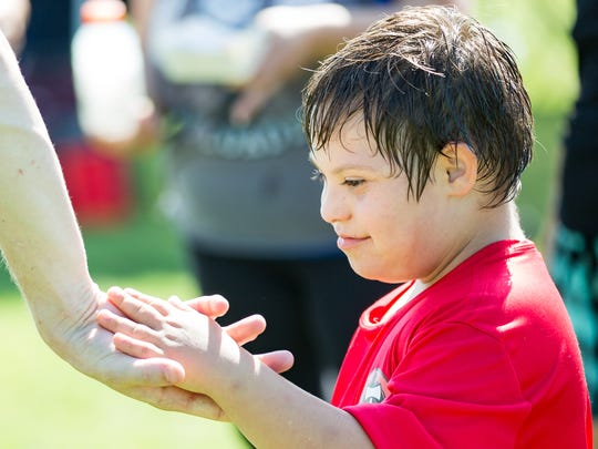 Javery Edwards, 8, looks down at the hand of his coach Avery Neal,  while he holds it on Saturday, August 26, 2017, during the Las Cruces Timbers Football Club's soccer camp for special needs kids.