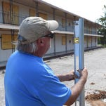 Rob Mapes, of Arkansas Fence Works in Harrison, checks the level on a fence post Friday at Creekside Apartments. Mapes and his crew are in the process of installing security fencing at the apartments. Mountain Home City Council agreed to not pursue condemnation of the complex after receiving a $50,000 cash bond from the owners.