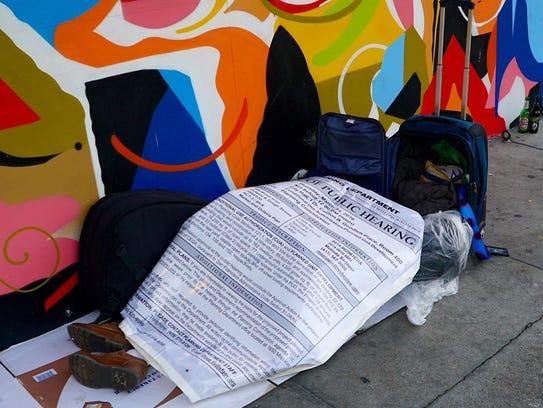 A homeless man in San Francisco huddles beneath a sign