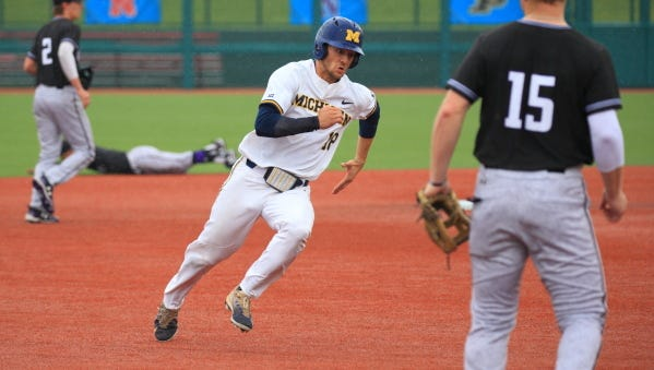 Michigan's Jake Bivens, who had reached on a double, scores on a single by Nick Poirier in the second inning.