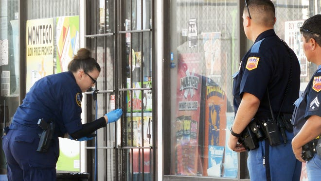 An El Paso police crime scene investigator on Wednesday morning looks for evidence on the door of a convenience store on the 1400 block of Paisano Drive in South El Paso near Downtown.