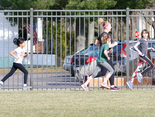 Teacher Kelly Wurzer runs along with some girls Tuesday