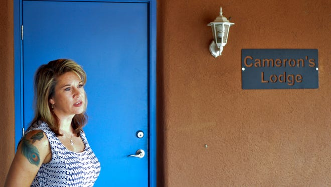 In this Aug. 9, 2016 photo, Jennifer Weiss-Burke, executive director of a youth recovery center in Albuquerque, N.M., stands by one of the rooms at the recovery center named after her son, Cameron Weiss. He died of a heroin overdose in 2011. Weiss-Burke said her teenage son's descent into drug addiction started with an opioid prescription a doctor wrote for him for a wrestling injury.
