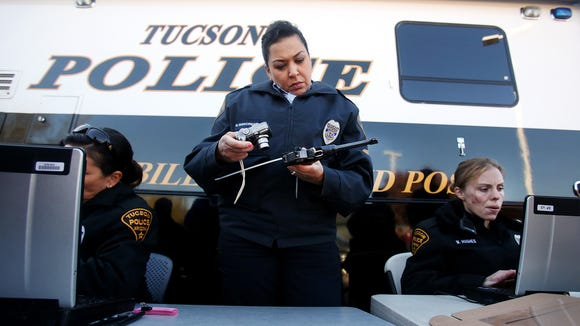 Officer Monica Vannorman photographs a pistol as officer Merri Hughes (right) logs the relinquished weapons at a gun buyback event Tuesday, Jan. 8, 2013, at the Tucson Police Department Midtown Substation.