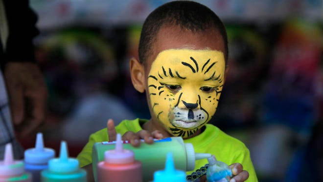 Four-year-old Kwesi Coley of Rochester makes sand art after getting his face painted as a tiger at the annual 19th Ward Community Square Fair last year. The event is held every year to promote community.