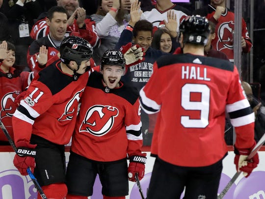 New Jersey Devils defenseman Will Butcher, center,