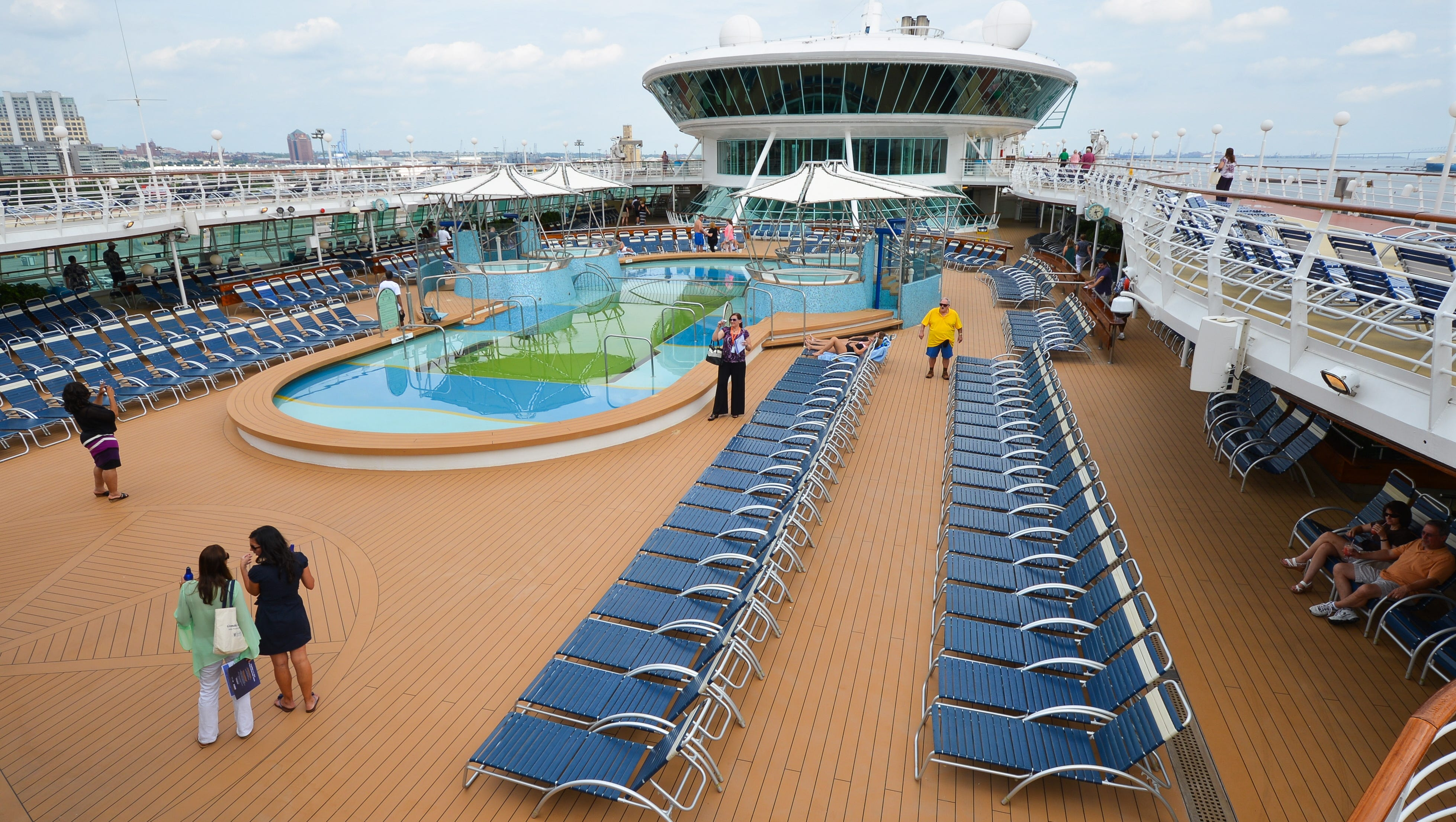 Grandeur of the Seas' pool deck is lined with dozens of lounge chairs.
