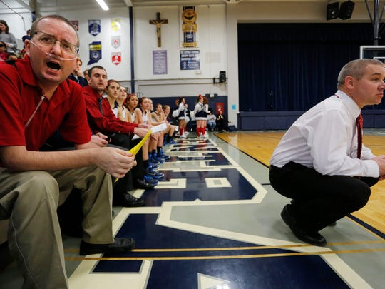 Central Catholic assistant girls basketball coach Jeff Dienhart, left, shouts encouragement to the Knights. At right is coach Craig Devault.