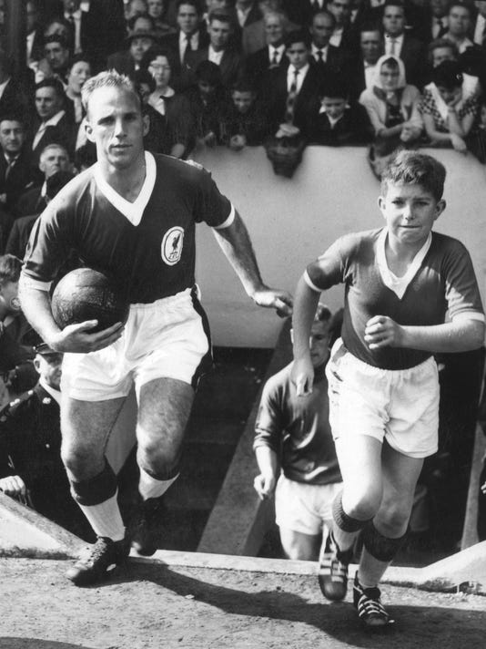 FILE -  In this Jan. 28, 1960 file photo, Liverpool captain Ronnie Moran leads his team out onto the Anfield pitch, accompanied by the team's lucky mascot, 14-year-old David Goodman, in Liverpool. Moran, a former title-winning Liverpool player who became an integral part of the coaching staff as the club dominated English soccer, has died, it was announced on Wednesday, March 22, 2017. He was 83. (PA via AP, File)