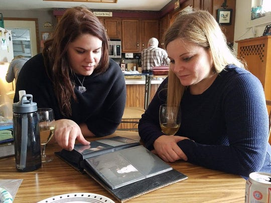 Amanda Anderson (right) and her new sister, Erin Linder, look over family photos.