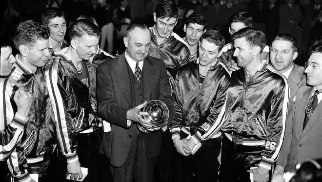 In this March 26, 1949, file photo, University of Kentucky basketball coach Adolph Rupp and his team admire the NCAA basketball title cup after defeating Oklahoma A&M 46-36 in Seattle. Front row, left to right are: Jim Line, Walter Hirsch, Coach Rupp; Ralph Beard, and Clifford Barker. Star center Alex Groza looks over Rupp's shoulder. The Associated Press is ranking the top 100 college basketball programs of all time using 68 years of data from the AP Top 25 poll.