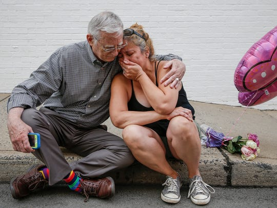 "Charlottesville resident Mai Shurtleff, right, sits weeping on the sidewalk near the site where on Saturday a car plowed into a group of counter protesters killing one. ""This wasn't something I expected to happen in our town,"" she said, as Charlottesville resident Bob Kiefer consoled her on August 13, 2017. ""This does not define Charlottesville at all. We are a strong, loving community. I don't even know this gentleman but as strangers we are friends. This is what makes us stronger together."""