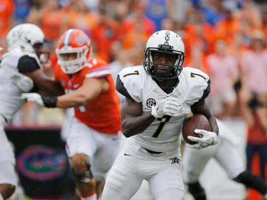 Commodores running back Ralph Webb (7) runs with the ball against the Florida Gators during the first quarter at Ben Hill Griffin Stadium.