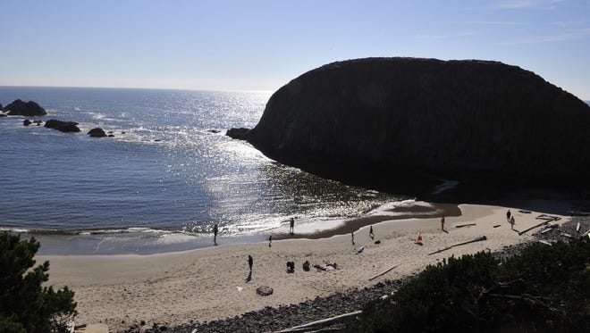 Visitors walk along the beach at Seal Rock State Recreation Site near Newport in this file photo.